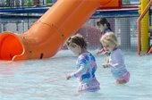 Two little girls standing in the water at The Splash Zone