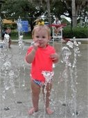 A toddler standing with water spraying up around her