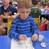 A young boy doing a project with toothpicks and marshmallows.