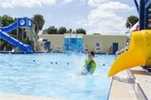 A boy splashing into the pool from a water slide.