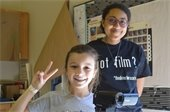 A girl doing the peace sign and holding a camera with her instructor
