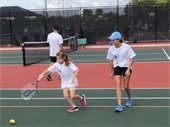 A girl learning to play tennis with an instructor