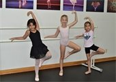 Three young girls in ballet poses