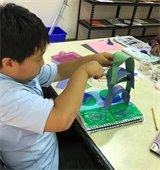 A young boy making a paper sculpture