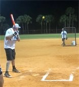 A man pitching a softball to another man with a bat