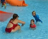 Two young children with a lifeguard in the Splash Zone