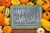 """A chalkboard surrounded squash with the words """"Happy Thanksgiving"""" written on it in chalk."""