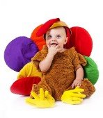 A toddler sitting in a turkey costume