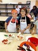 Two boys wearing aprons and bandanas preparing food
