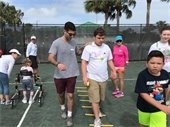 Volunteers helping special needs participants learn tennis