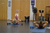 Two women on floor mats doing crunches