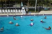 A group of adults in the pool taking a water aerobics class.