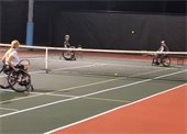 Three people in wheelchairs playing tennis