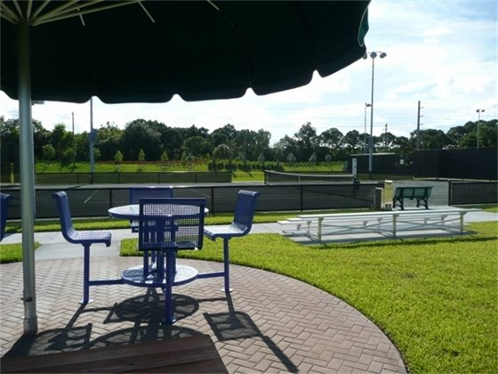 a view of seating with an umbrella and tennis court in the background