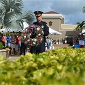A member of the Police Department carrying a flower wreath