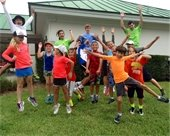 Tennis camp counselors and campers jumping in the air
