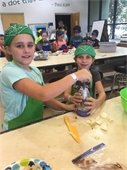 Two kids wearing bandannas and aprons and chopping onions
