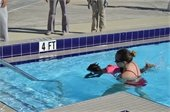 A little girl getting a swim lesson from an instructor in the pool.