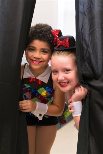 Two young girls in dance costumes peering out between the curtains.