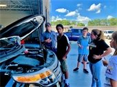 A small group of teens standing in front of a car with a mechanic.