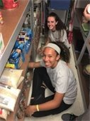 Two teenage girls sorting food at a food bank.