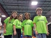 Three girls and a boy wearing camp t-shirts.