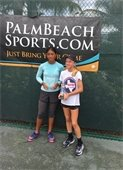 Two girls holding tennis trophies.