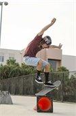 A teenage boy doing a trick on a skate board.