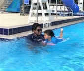 A lifeguard giving a little girl a swim lesson.