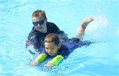 A lifeguard giving a little boy a swim lesson.