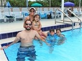 A family of two adults and three kids in the pool.