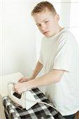 A boy ironing a shirt.