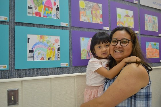Mother and daughter in front of artwork.