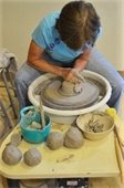A woman working with clay on a pottery wheel.