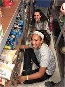 Two teenage girls sorting food.