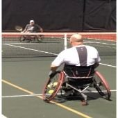 Two wheelchair tennis players on the tennis court.