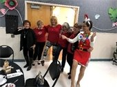 Six ladies dancing at the Annual Holiday Senior Luncheon.