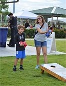 A mom and son playing cornhole.