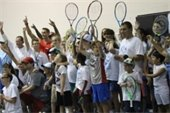 A group of people holding up tennis rackets.