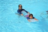 A swim instructor giving a young girl a swimming lesson in the pool.