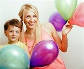 A mom and son holding balloons.