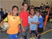 Four boys wearing soccer outfits and holding a soccer ball.