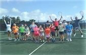 A group of kids and tennis instructors jumping in the air on a tennis court.