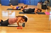 Three women doing a floor workout on mats.
