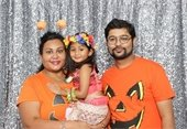 A family of three in Halloween costumes.