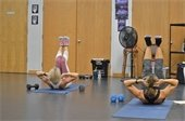 Two women exercising on floor mats.