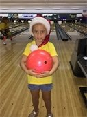 A young girl wearing a Santa hat and holding a bowling ball.