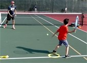 A young boy and a tennis instructor on the tennis court.