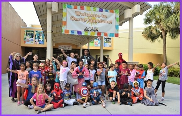 A group of kids and camp counselors dressed in super hero costumes.