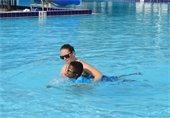 A lifeguard giving a young boy a swimming lesson in the pool.